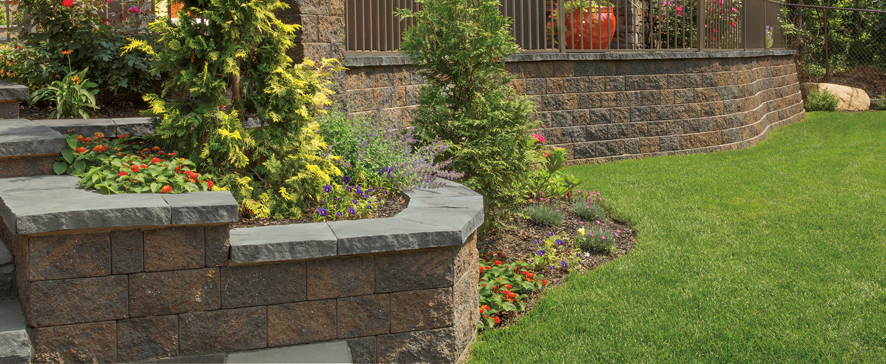 Retaining wall with landscaped lawn and plant beds