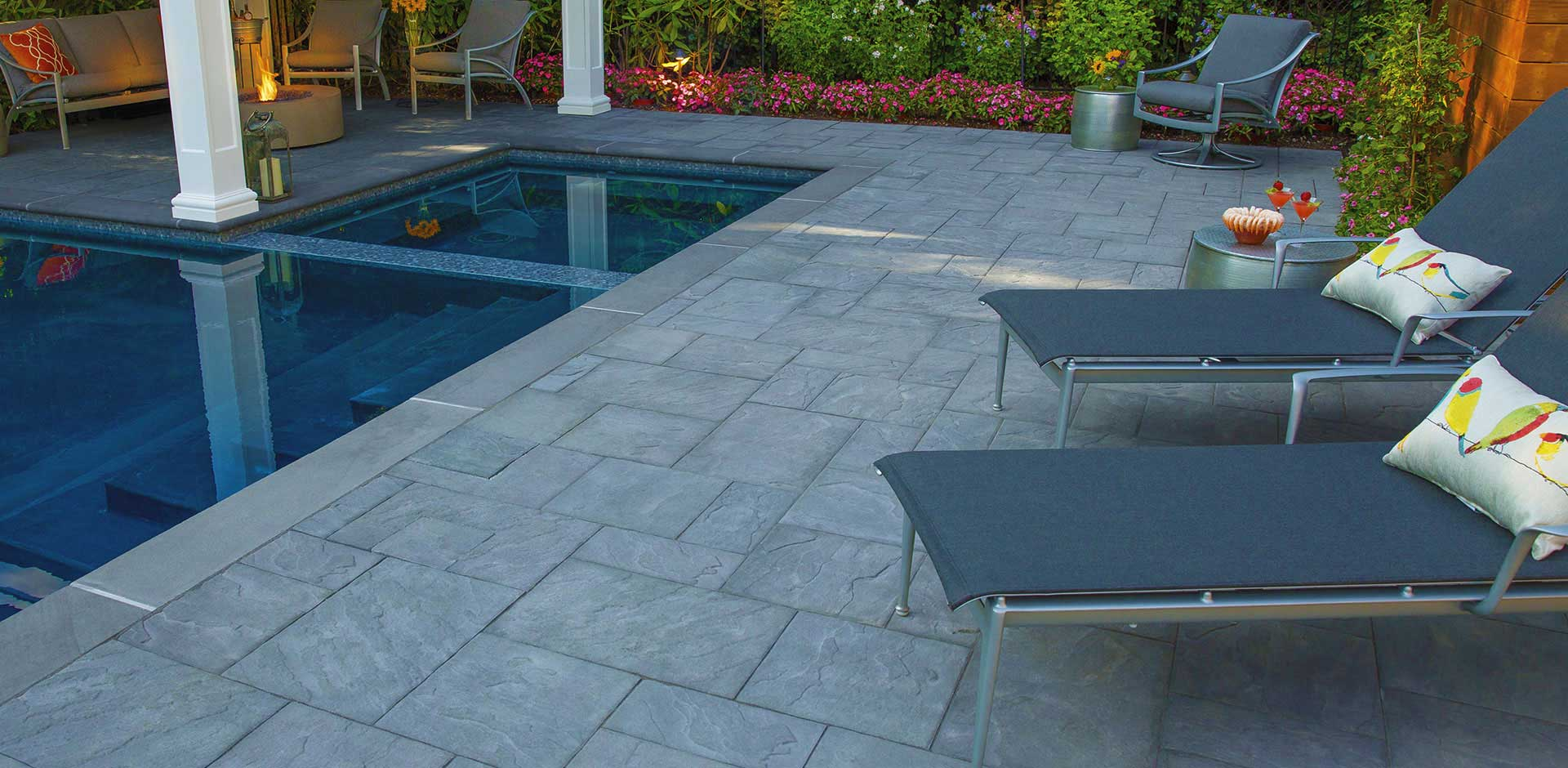 Blue tinted pavers of large square and rectangular shapes used around pool