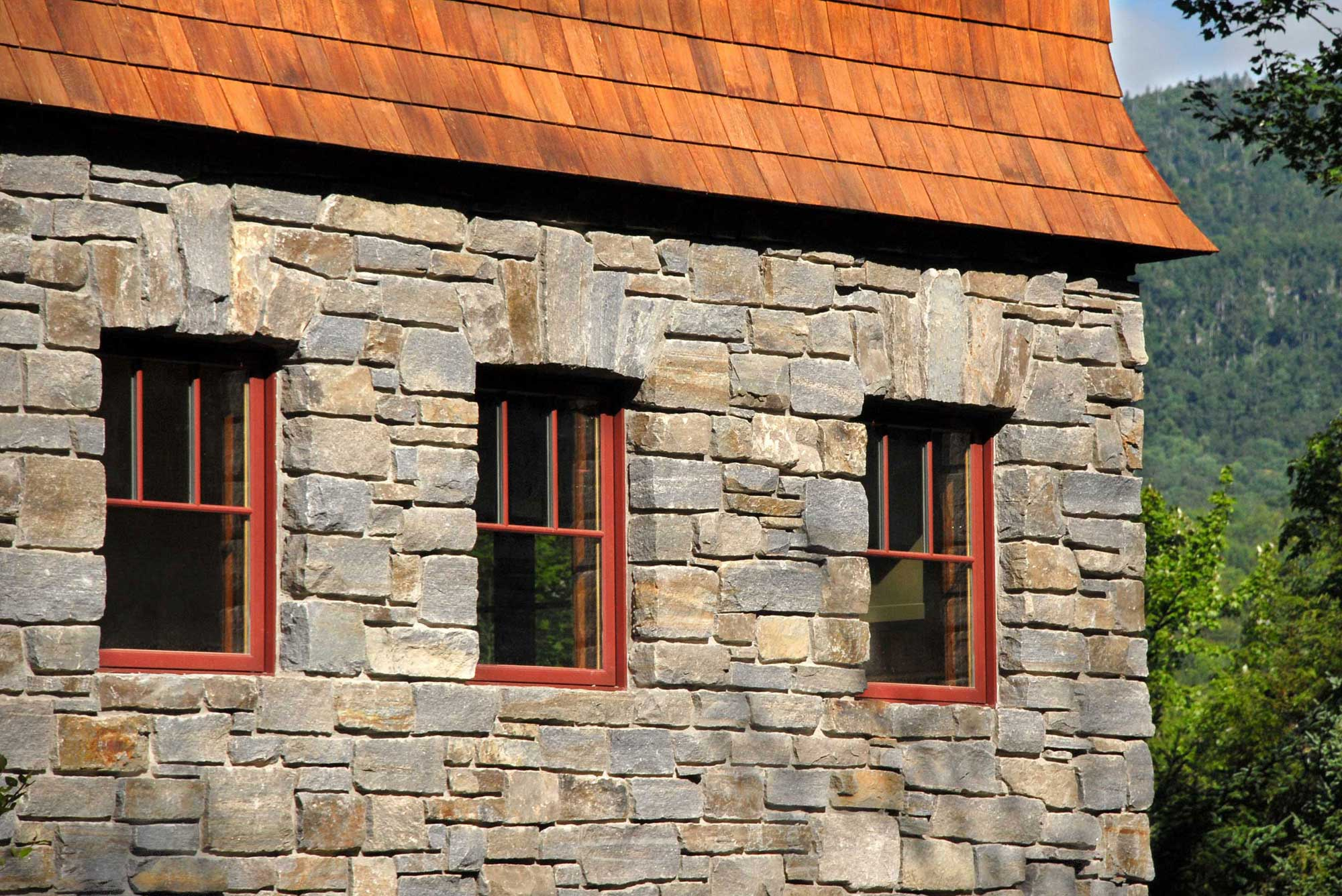 Granite blocks are used for the side of this home with three windows in the middle