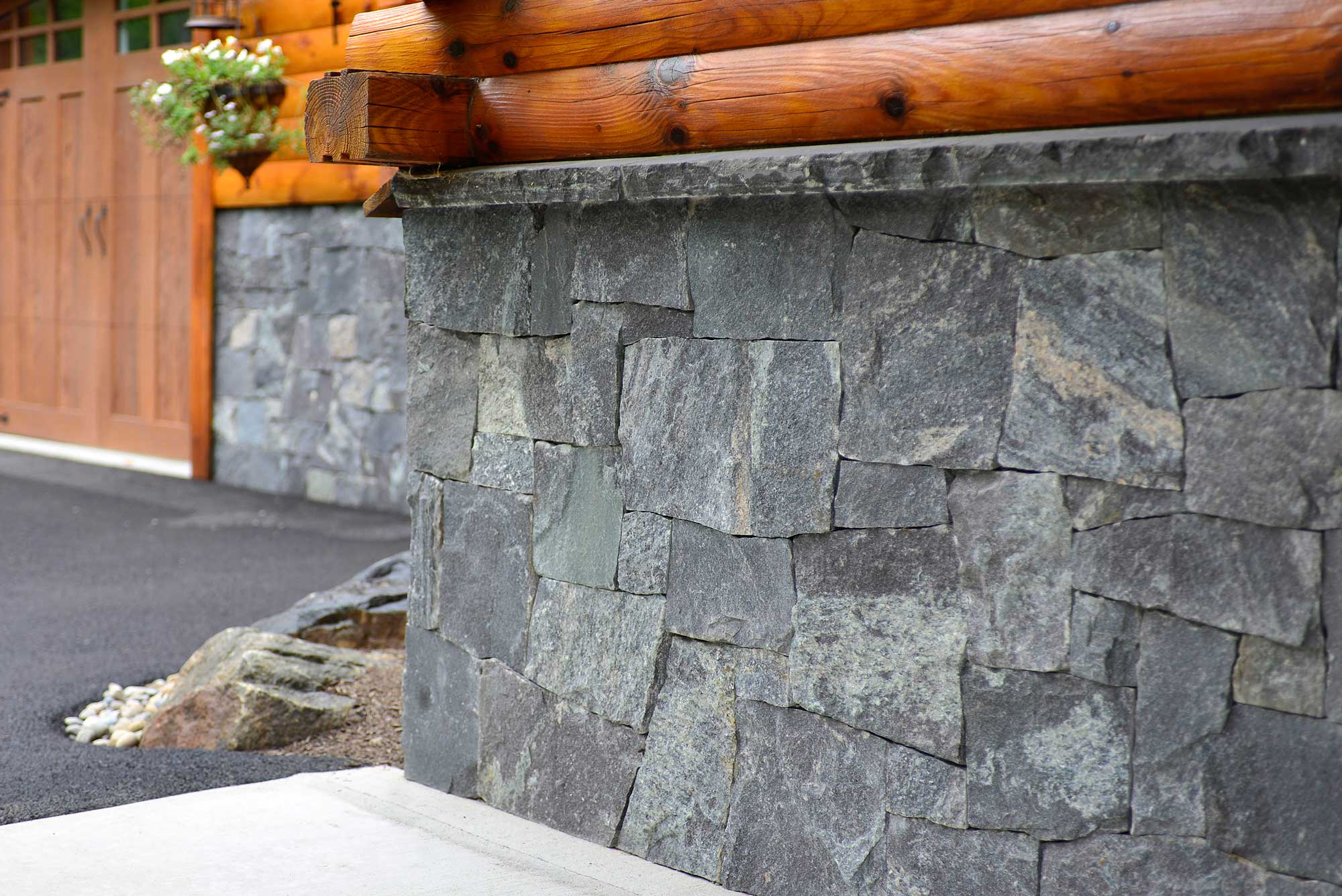 Tightly fit granite stone exterior wall with wood siding on top