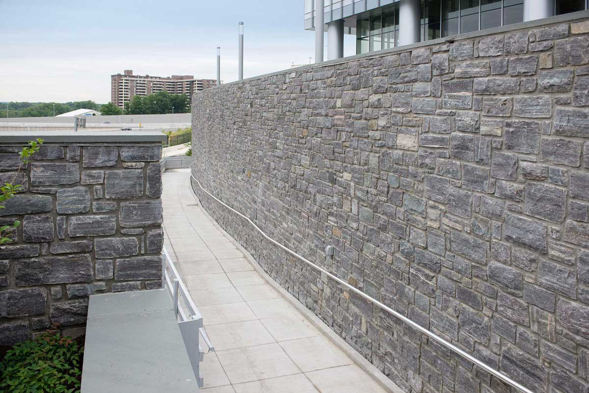 Gray stones used for large wall along a walking path