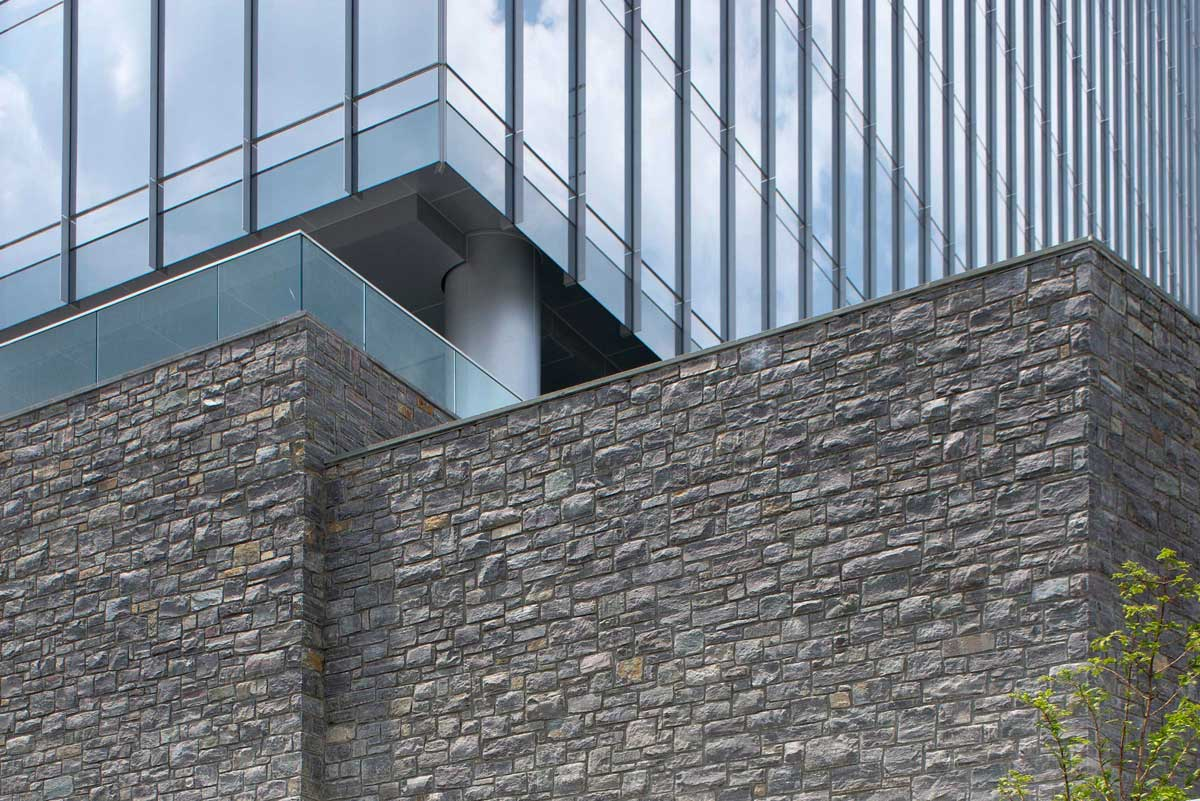 Gray granite stones used for wall under glass building