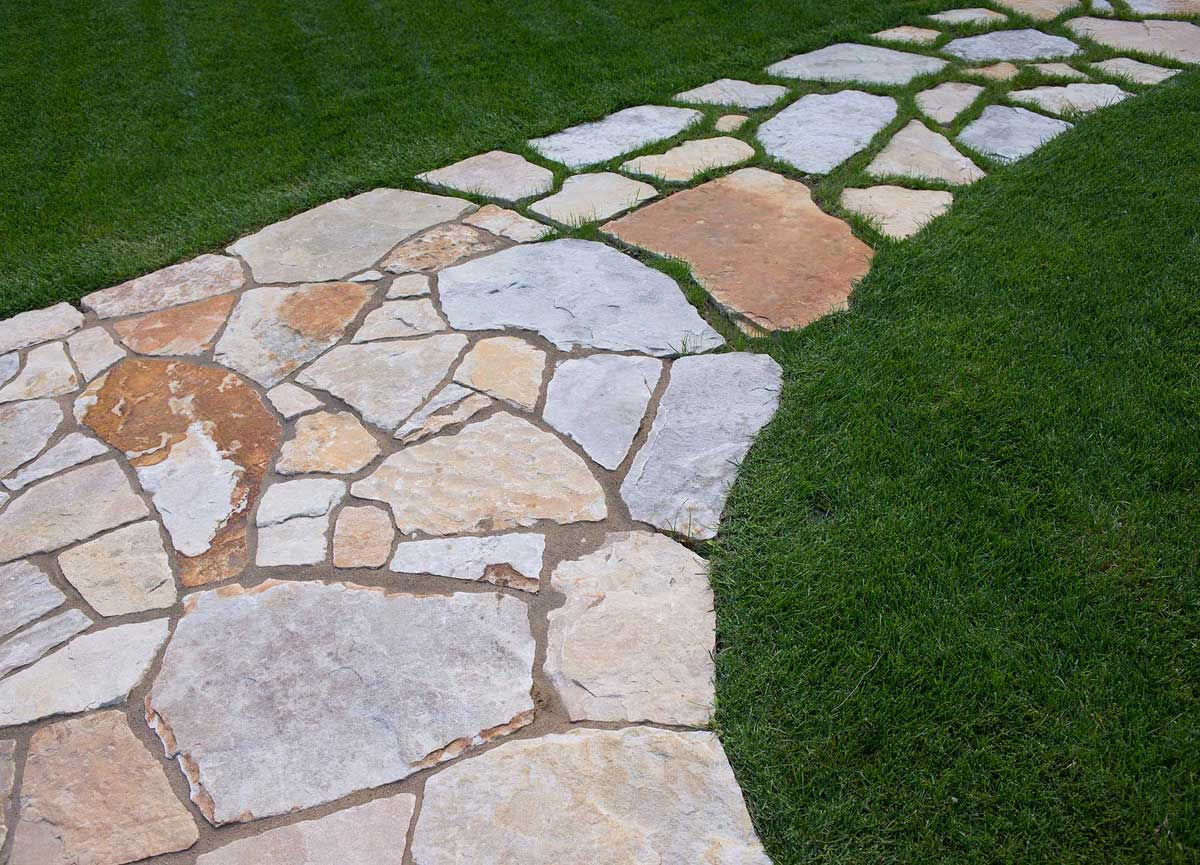 Flagstone laid out in path with green lawn on both sides