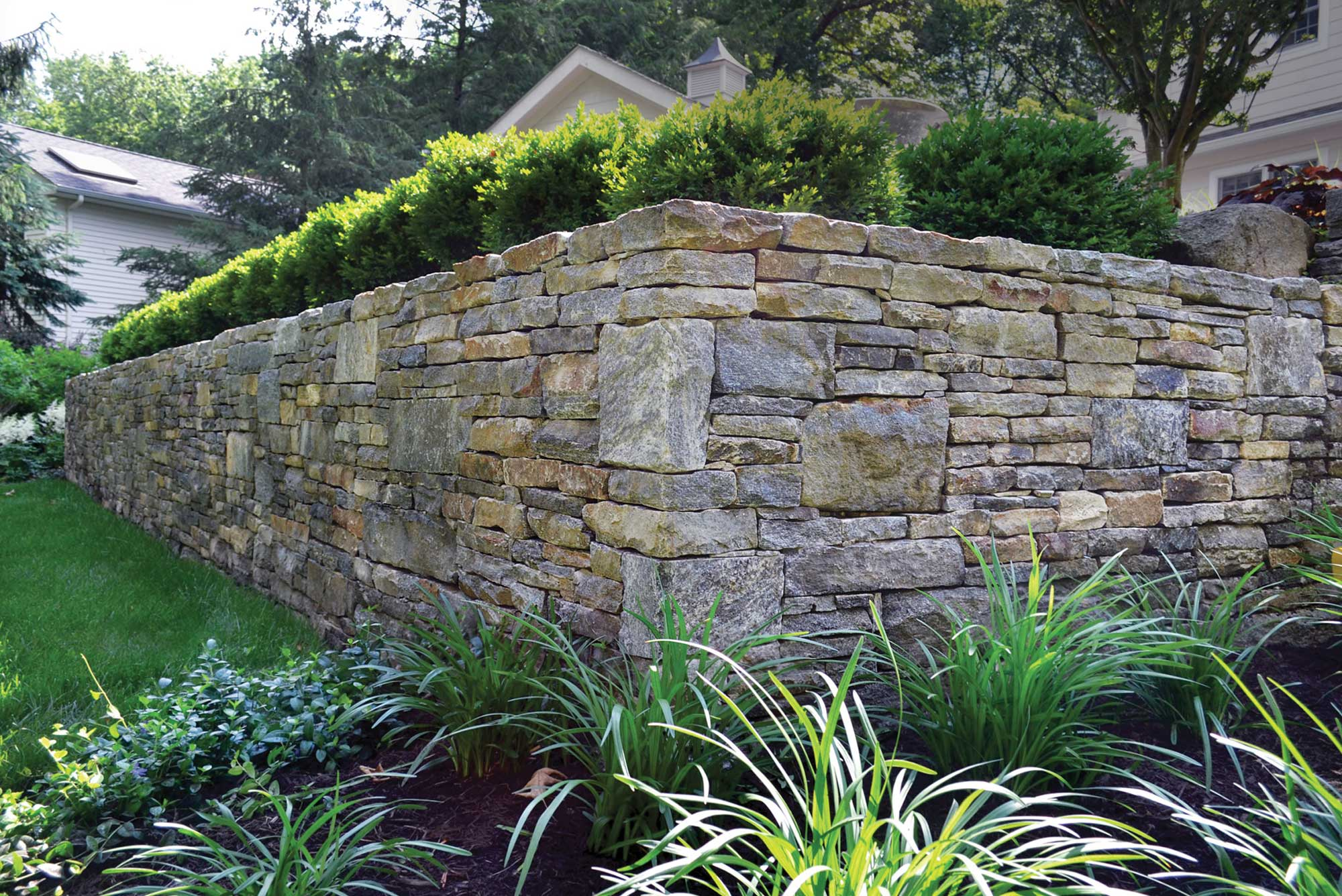 Corner of tall retaining wall with bushes on top and landscaped garden in front