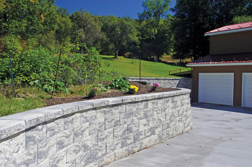 Retaining wall along driveway with trees to the left