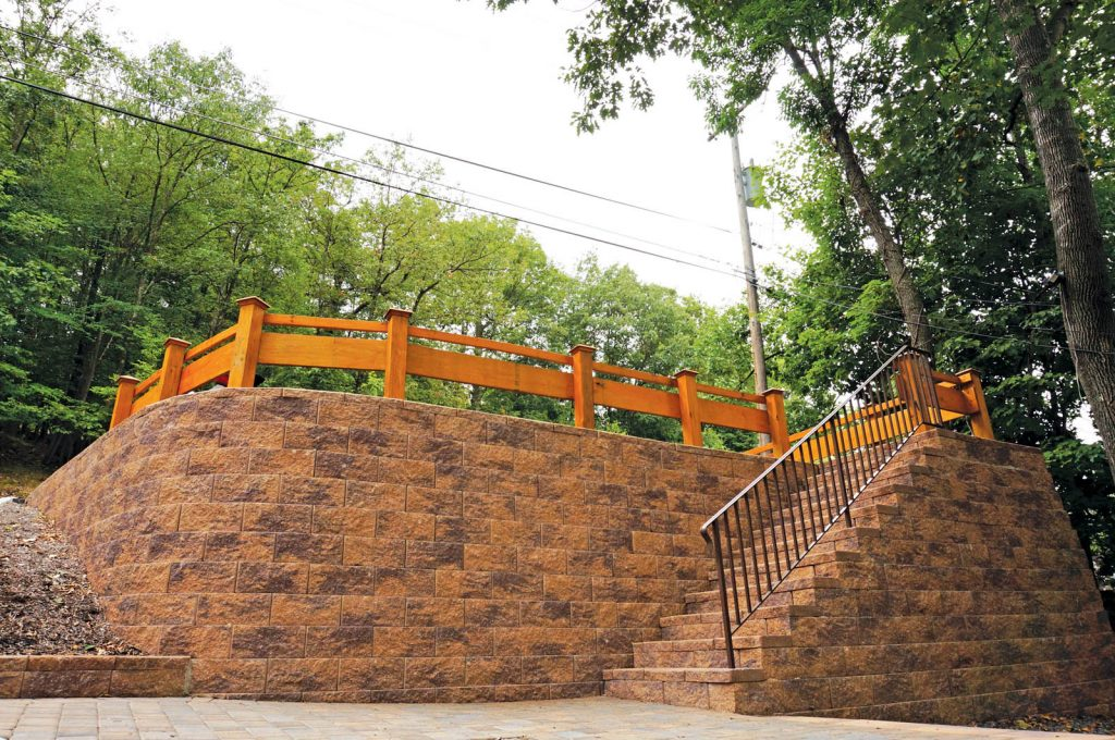 Light brown colored retaining wall with stairs that have an iron railing