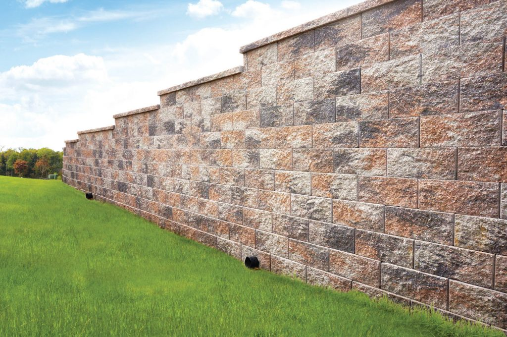 Large blocks in tall retaining wall with grass field on left