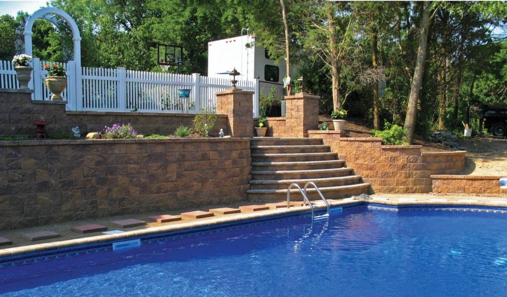 Retaining walls with stairs lead down to a pool