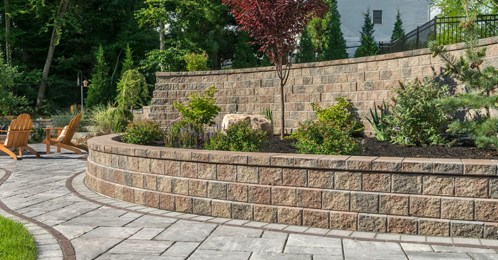 Two tier retaining walls built with Unilock Concord wall systems with trees and bushes on first level