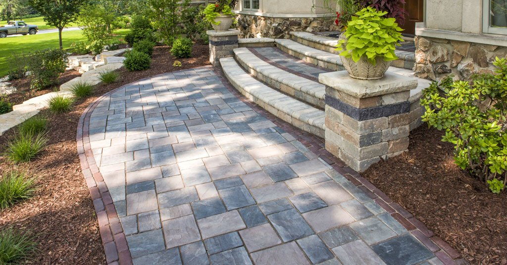 Square and rectangular pavers with reddish tint used for walkway to front of home