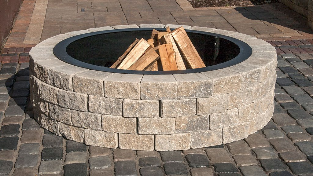 Circular fire pit with chopped wood stacked in the middle