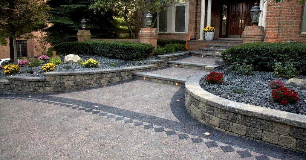 Front entrance to large home has walkway and stairs made with Unilock Series pavers