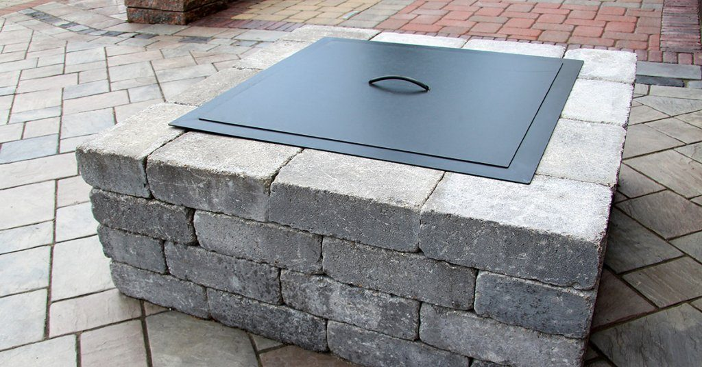Square shaped fire pit with black metal cover on top