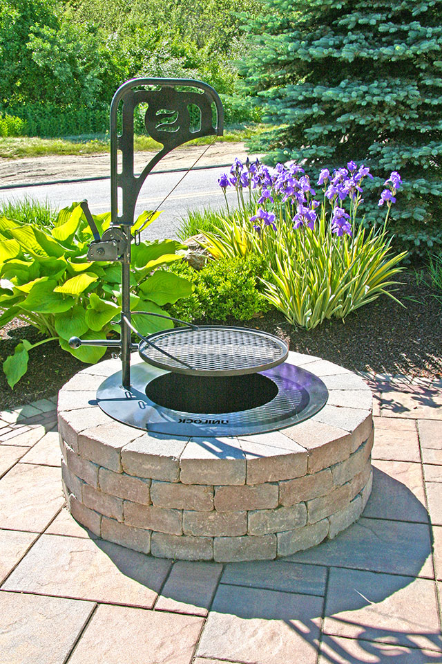Circular Unilock fire pit with a grate hovering over the top.