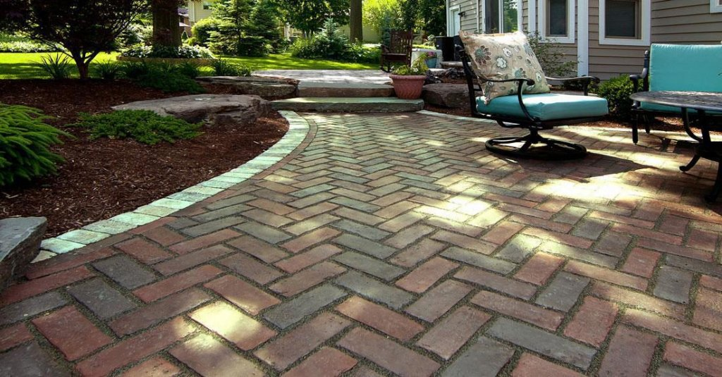 Outdoor backyard patio made with red colored Unilock Town Hall pavers