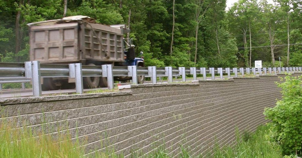 Retaining wall with road on top that has a truck driving on it