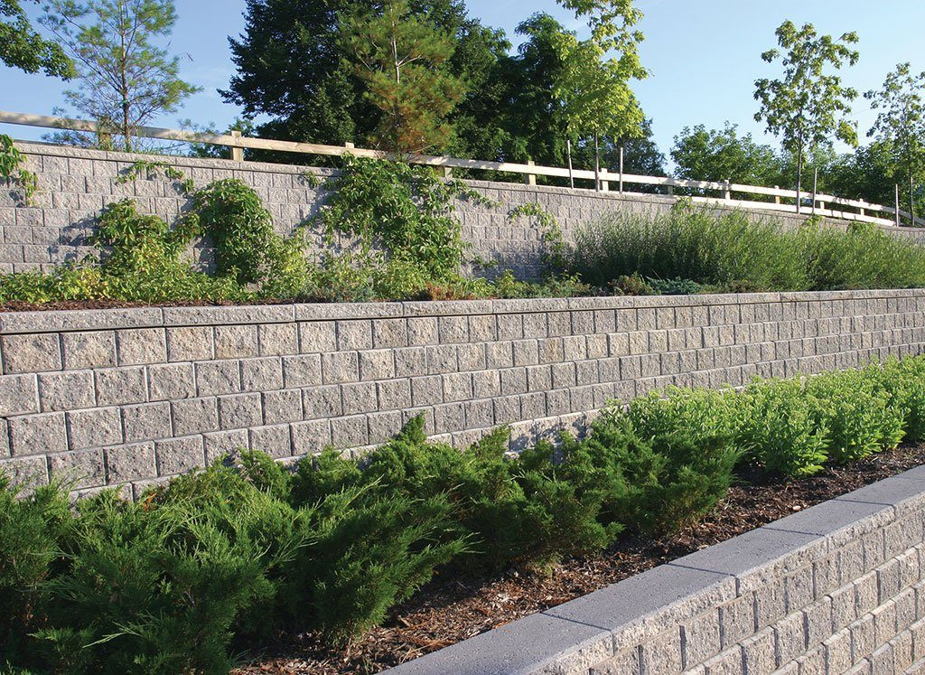 Three tier retaining walls built with Unilock Concord wall systems with trees and bushes on first and second levels