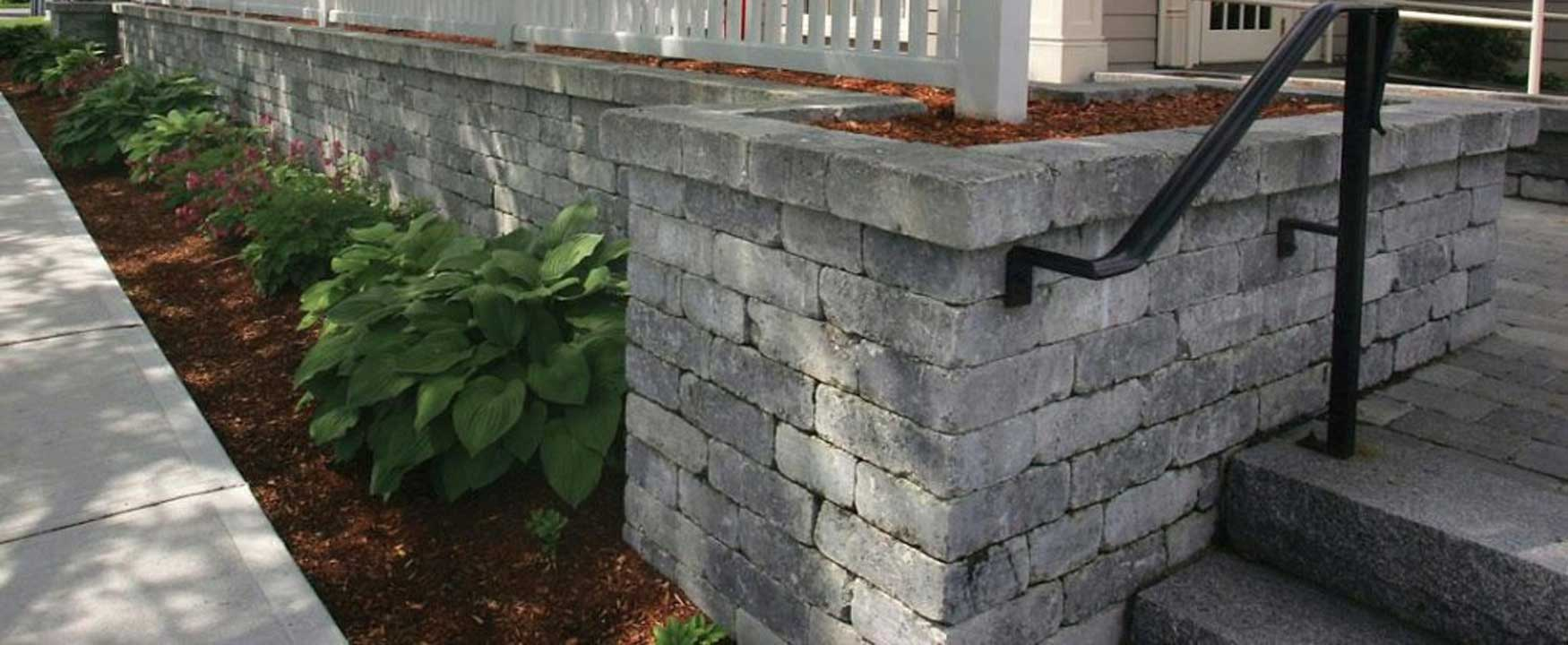 Wall made with light gray Unilock pavers