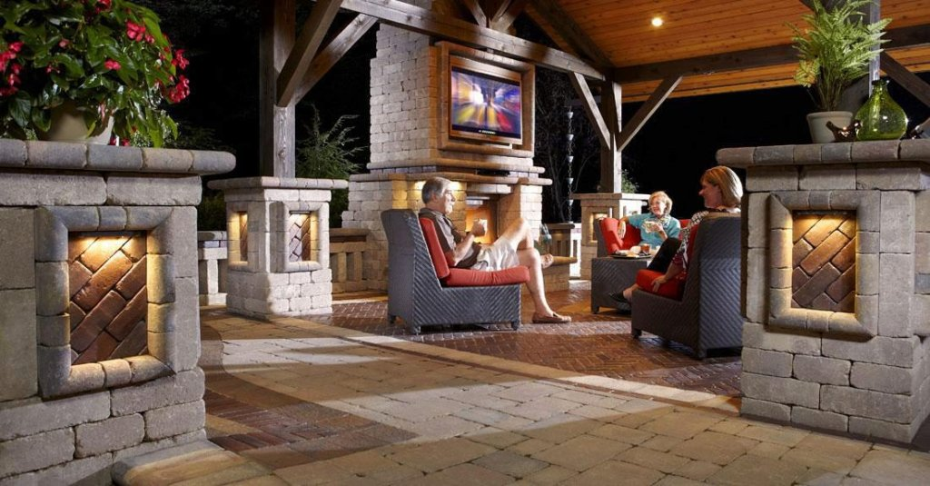 Outdoor living space with people sitting in chairs surrounded by wall system pillars and outdoor fireplace