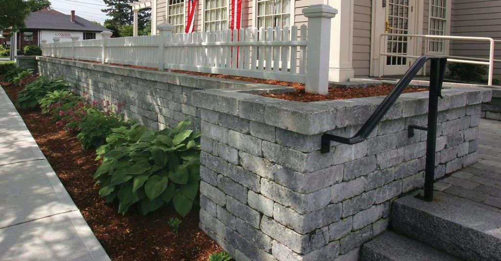 Gray colored blocks wall system around a home with plants in front
