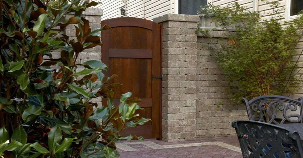 Tall wall system along side of house with door between two pillars